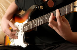 Guitarist. Close up of a guitar player sat playing the electric guitar royalty free stock images