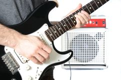 Guitarist and Amp. Guitarist playing a solo with the amp in the background Royalty Free Stock Image