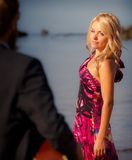 Guitarist back-view and blonde girl against sea Royalty Free Stock Photos