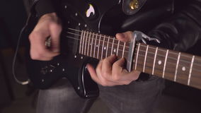 Guitarist with black musical instrument on the concert or try-out indoors stock footage