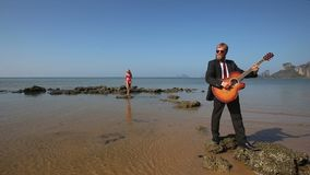 Guitarist plays masterly on rock at beach for blonde girl stock video footage