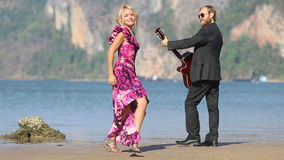 Guitarist and blonde girl look at each other following around stock footage