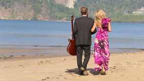 Guitarist and blonde girl walk towards sea points to sky stock video footage