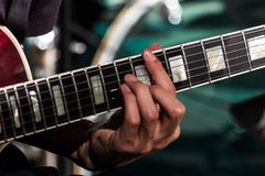 The guitarist clamped the chord on the electric guitar fretboard. Blured. Stock Photography