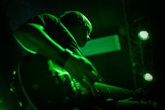 Guitar player in green light. Guitarist at a concert with green lighting, closeup, bottom view Stock Image