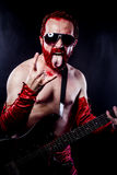 Guitarist with electric guitar black, wearing face paint and red Royalty Free Stock Images