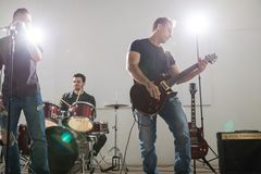 Guitarist grooving music on stage. Young rock band guitarist playing guitar on stage with band members at music concert Royalty Free Stock Photos