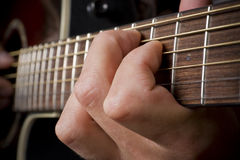 Guitarist hand playing acoustic guitar. Musicians hand playing acoustic guitar stock image