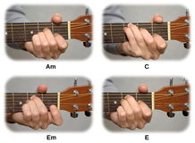 Guitarist hand playing guitar chords: Am, C, Em, E royalty free stock images