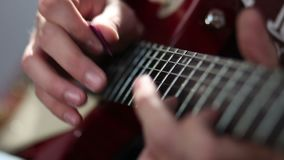 Guitarist hand strumming at electric guitar string stock footage