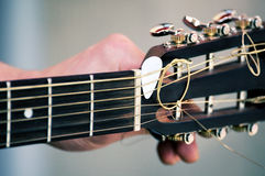 Guitarist hand tuning classic acoustic guitar. Hand tuning a guitar from headstock Royalty Free Stock Photo