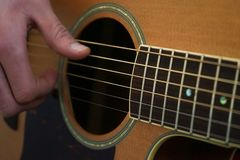 Guitarist hands and guitar close up. Guitarist playing classic acoustic guitar with his fingers, finger-picking style royalty free stock photos