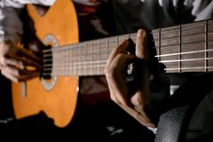 Guitarist hands and guitar close up. Playing classic guitar. Play the guitar. Low key image stock photography