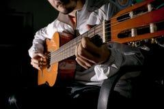 Guitarist hands and guitar close up. Playing classic guitar. Play the guitar. Low key image stock photos