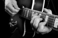 Guitarist hands and guitar close up. playing electric guitar. play the guitar. black and white. stock image