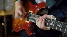 Guitarist hands playing electric guitar on concert stage