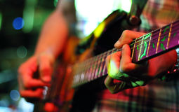Guitarist hands playing guitar. Only one hand and guitars neck are in focus stock images