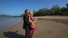 Guitarist helps blonde girl play guitar then points forward stock footage