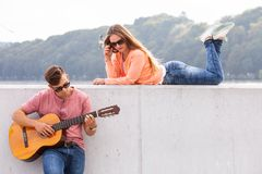 Guitarist and his muse. Love romance music talent passion dating concept. Guitarist and his muse. Young men playing guitar with girl lying on wall with scenery royalty free stock photography