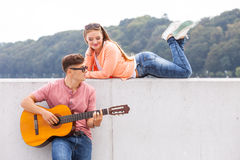 Guitarist and his muse. Love romance music talent passion dating concept. Guitarist and his muse. Young men playing guitar with girl lying on wall with scenery Stock Image