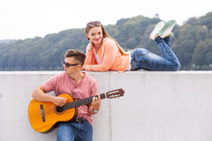 Guitarist and his muse. Love romance music talent passion dating concept. Guitarist and his muse. Young men playing guitar with girl lying on wall with scenery Stock Photo