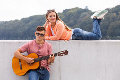 Guitarist and his muse. Love romance music talent passion dating concept. Guitarist and his muse. Young men playing guitar with girl lying on wall with scenery Royalty Free Stock Image