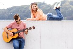 Guitarist and his muse. Love romance music talent passion dating concept. Guitarist and his muse. Young men playing guitar with girl lying on wall with scenery Stock Images