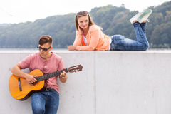 Guitarist and his muse. Love romance music talent passion dating concept. Guitarist and his muse. Young men playing guitar with girl lying on wall with scenery Royalty Free Stock Photo