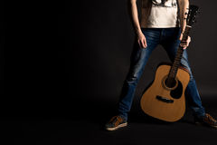 Guitarist holding his left hand with an acoustic guitar on a black isolated background Royalty Free Stock Images