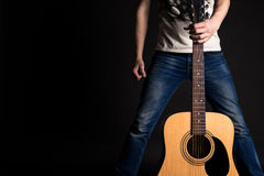 The guitarist holds his left hand with an acoustic guitar in front of him, on a black isolated background Stock Images