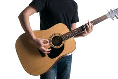 Guitarist in jeans and a black T-shirt, playing an acoustic guitar with a slider, on the left side of the frame, on a white backgr Royalty Free Stock Image