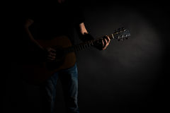 The guitarist in jeans plays an acoustic guitar, on the left side of the frame, on a black background. Horizontal frame Royalty Free Stock Image