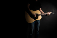 The guitarist in jeans plays an acoustic guitar, on the right side of the frame, on a black background. Horizontal frame Stock Photography