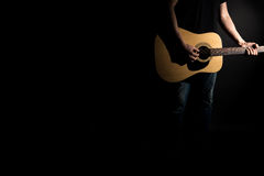 The guitarist in jeans plays an acoustic guitar, on the right side of the frame, on a black background. Horizontal frame Stock Photo