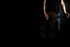 The guitarist in jeans plays an acoustic guitar, on the right side of the frame, on a black background. Horizontal frame Stock Photos