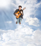 Guitarist Jumping in the Clouds Stock Image