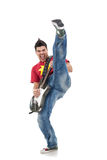 Guitarist kicking while performing Royalty Free Stock Photography