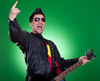 Guitarist making a rock and roll gesture royalty free stock photography