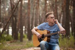Guitarist man talks phone forest concept. Work discussion. In-demand successful musician Royalty Free Stock Photos