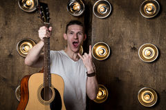 Guitarist, music. A young guy is standing with an acoustic guitar in his hand, in the background with lights behind him. Horizonta Royalty Free Stock Photos