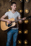 Guitarist, music. A young man plays an acoustic guitar on a background with lights behind him. Vertical frame Stock Photography