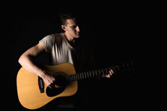 Guitarist, music. A young man plays an acoustic guitar on a black isolated background. Horizontal frame. Guitarist, music. A young man plays an acoustic guitar Stock Photos