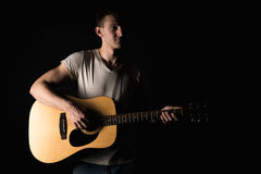 Guitarist, music. A young man plays an acoustic guitar on a black isolated background. Horizontal frame Stock Photos