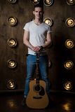 Guitarist, music. A young man stands with an acoustic guitar in the background with the lights behind him. Vertical frame Royalty Free Stock Images