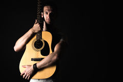 Guitarist, music. A young man stands with an acoustic guitar on a black isolated background. Horizontal frame Stock Image