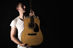Guitarist, music. A young man stands with an acoustic guitar on a black isolated background. Horizontal frame Royalty Free Stock Photo