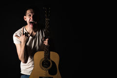 Guitarist, music. A young man stands with an acoustic guitar and shows his tongue and fingers on a black isolated background. Hori Royalty Free Stock Photo