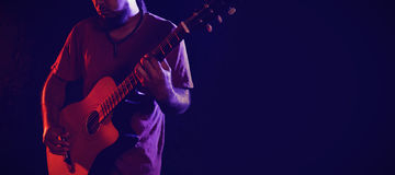 Guitarist performing in club. Male guitarist performing at nightclub Royalty Free Stock Image