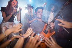 Guitarist performing by crowd at nightclub. Low angle view of guitarist performing by crowd at nightclub Royalty Free Stock Image