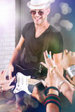 Guitarist performing for his adoring fans. A guitarist performing for his adoring fans at  dico club or party Stock Photography